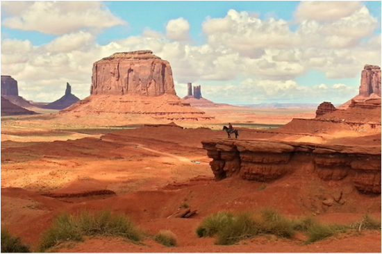 a Navajo sitting on his horse looking out over Monument Valley, Arizona